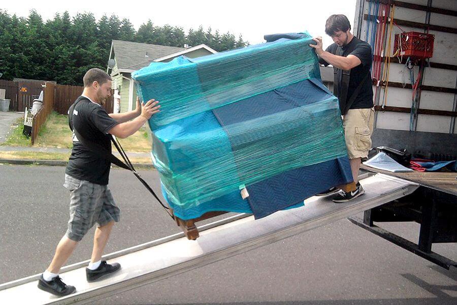 Mannen laden zwaar meubel in verhuiswagen